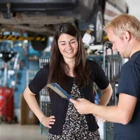 Young mechanic and woman looking at notepad and smiling in garage